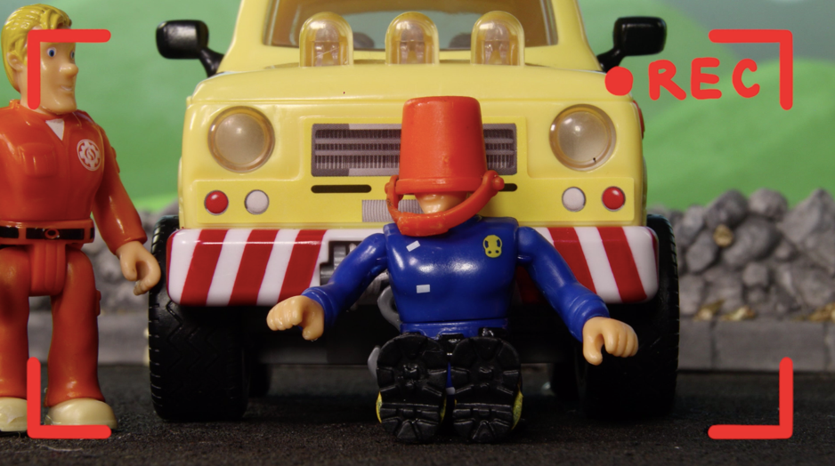Fireman Sam sitting in front of his truck wearing a red bucket on his head.