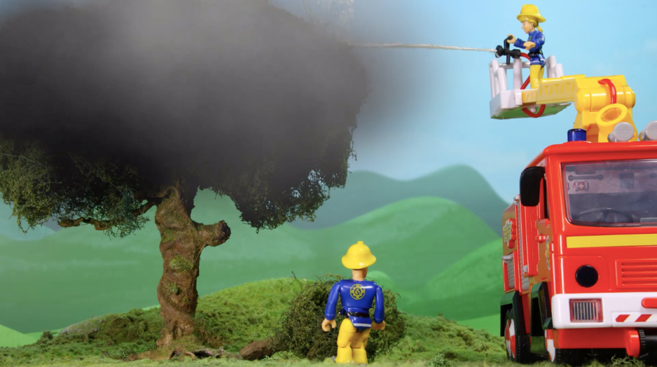 Fireman Sam and friend spraying water from the firetruck to extinguish a tree on fire