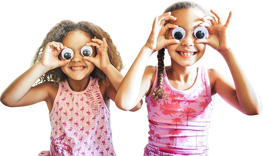 two girls in pink tops holding googly eyes over their eyes and smiling