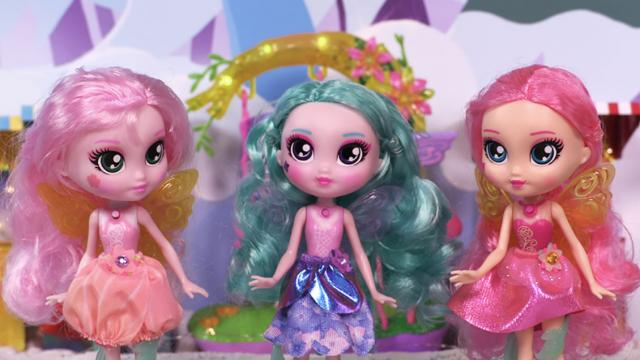 3 sparkly faery dolls posed in front of a playset