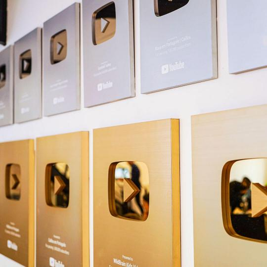 Two rows of rectangle shaped awards hanging on the wall.